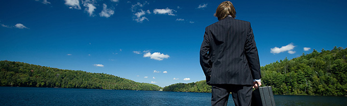 man with a briefcase looking at the lake and foothills